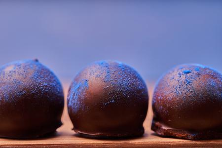 Chocolates with blue algae on blue background