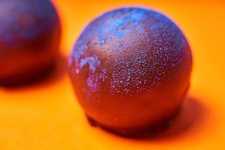 Chocolates with blue algae on colored background