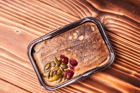 Turkey pate with pumpkin seeds and berries on a wooden table Stock Photo
