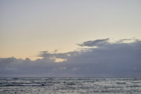 The beginning of sunrise over the ocean. Sea wave