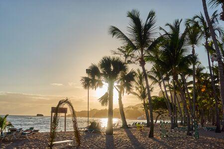 Sandy beach with palm trees and football goal. Sunrise over the beach.