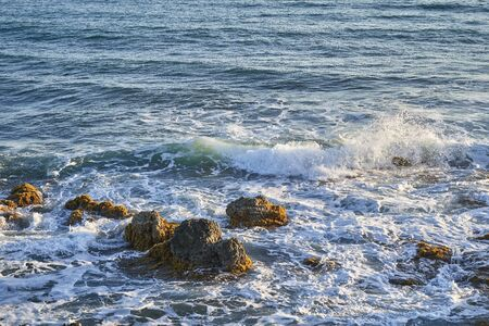 Ocean coast with rocks and waves at sunrise. Beautiful seascape.