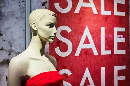Female mannequin in a shop window on the background of the inscription sale. Stockfoto