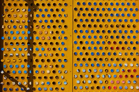 Yellow perforated metal sheets with round holes. Panel on mounting hardware.
