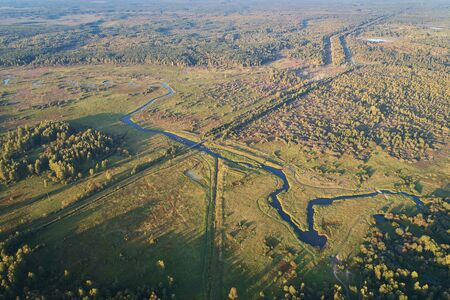 Aerial photography with a drone. Landscape with green forest, road and river