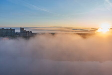 Fog over the city with the rising sun.