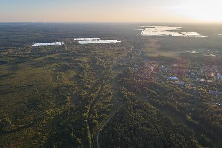 Aerial photography with a drone. Village with green forest, road and lake. Stok Fotoğraf