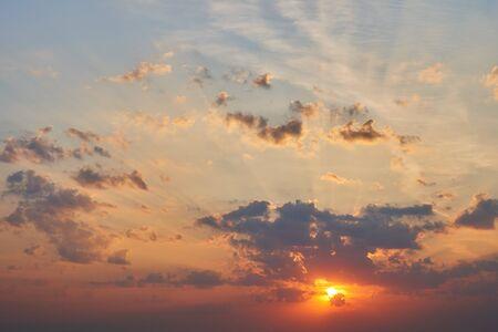 Salida del sol con rayos rompiendo las nubes.