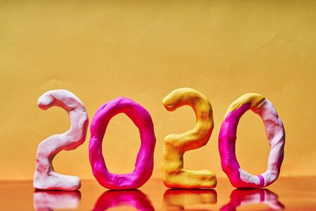 2020 New year design concept. Colored figures of plasticine on a yellow background.