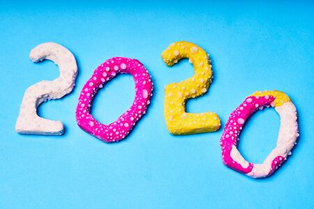 2020 New year design concept. Colored figures from plasticine on a blue background. Фото со стока