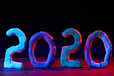 2020 New year design concept. Colored figures made of plasticine on a black background with mixed light.