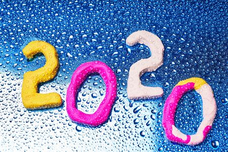 2020 New year design concept. Colored figures of plasticine on a blue background with water drops.