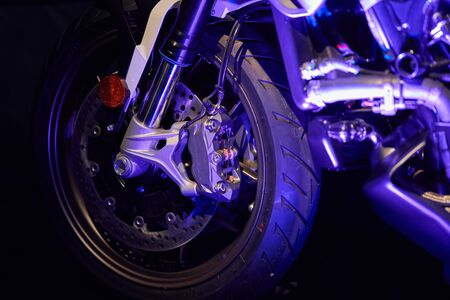 The front wheel of a modern motorcycle with blue lighting. Studio shooting
