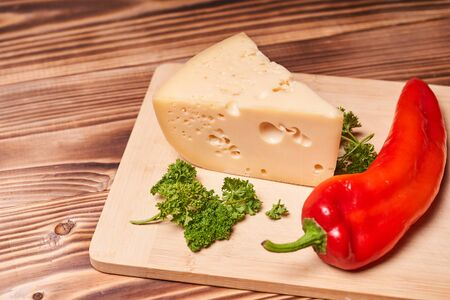 Maasdam cheese on a wooden table with herbs and red pepper.