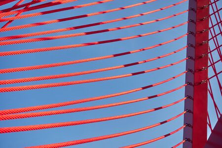 Abstract architectural features, steel beam with cables on sky background.