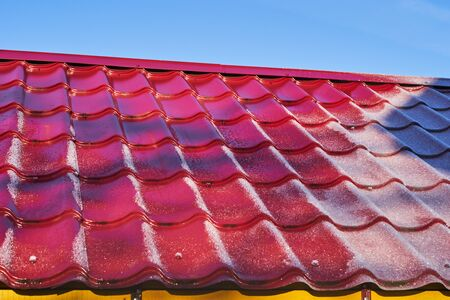 metal shingles and frost on the roof of the house on a Sunny day. Zdjęcie Seryjne