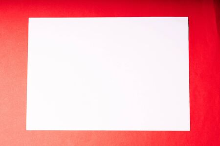 A white sheet of A4 paper on a red