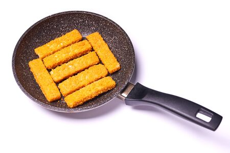 Pieces of fish in batter on a frying pan isolated on a white