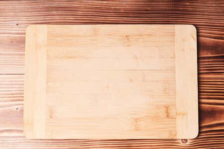 Bamboo kitchen Board on wooden table. The view from the top Kitchen utensil. Cooking food background.
