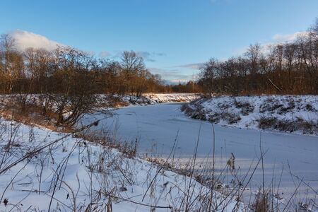 Beautiful winter landscape on a Sunny day with a frozen river. Banco de Imagens