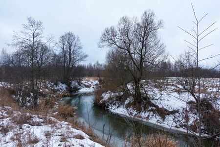 Spring landscape with river, ice and snow on the banks.
