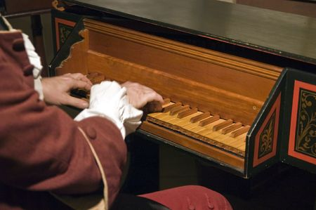 playing an antique harpsichord