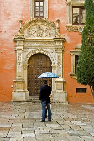 Young couple with umbrella,  standing in front of a church, chatting in the rain. Spain.