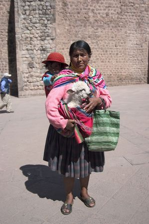 Cusco, Peru - August 2008 - Indian Woman with daughter and baby lama