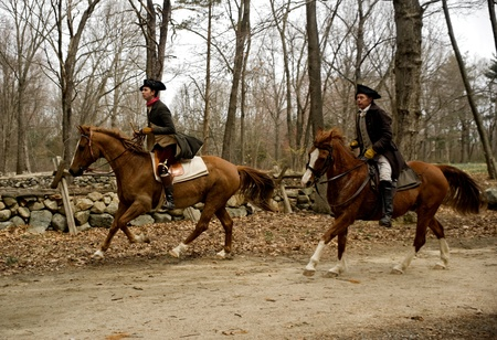 Concord, USA - April 16, 2011:  Minute Men ride horses on Battle Road in Concord, MA