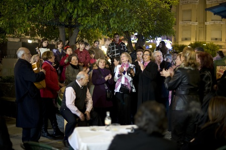 Spain, Cordoba - 3 January 2010: A group of neighbors are singing together in the front of their apartment building during the New Year holidays.