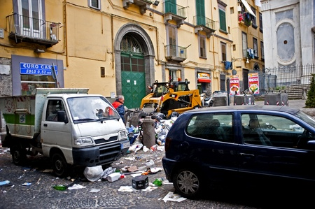 Naples, Italy - January 3, 2011: Trash collectors clean up Naples street from piles of garbage.