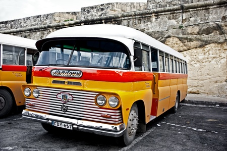 a classic yellow bus at the main bus station in Valetta.