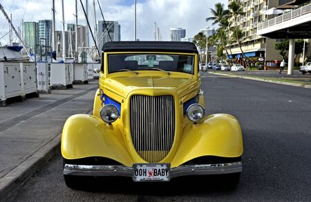 Honolulu-Hawaii, USA - December 6, 2011: Classic yellow car parked at a marina near downtown Honolulu.
