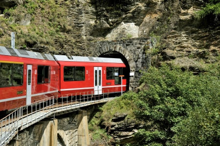 Commuter train is entering into a tunnel in the picturesque Swiss Alpes
