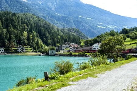 swiss culture: Commuter train is passing by a small village in the picturesque Swiss Alps. Stock Photo