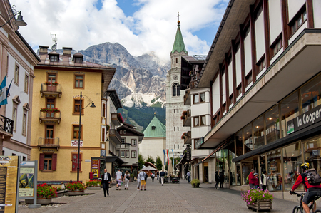 People are walking down the main street of alpine resort of Cortina dAmpezzo in the Italian Dolomites