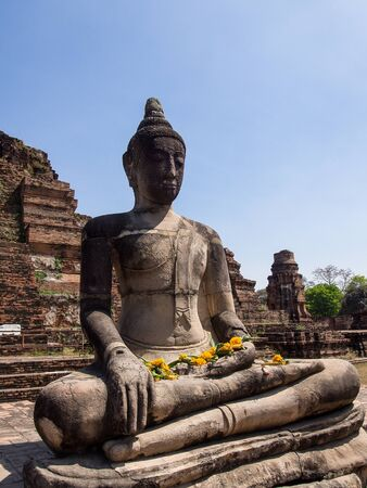 Asian religious architecture. Ancient sandstone sculpture of Buddha at Wat Mahathat ruins under sunset sky. Ayutthaya Thailand travel landscape and destinations photo
