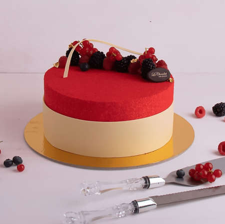 A red round strawberry flavoured cake on the plate, with strawberries topped, knives and strawberries spread on white background. Stok Fotoğraf