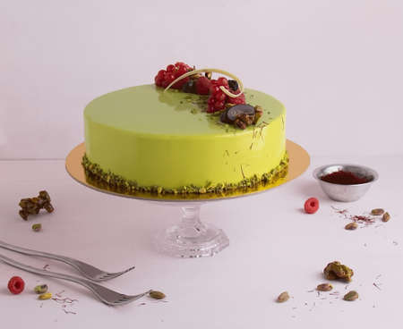 A round green strawberry flavoured cake on the stand, with strawberries topped, on the white background. Stok Fotoğraf