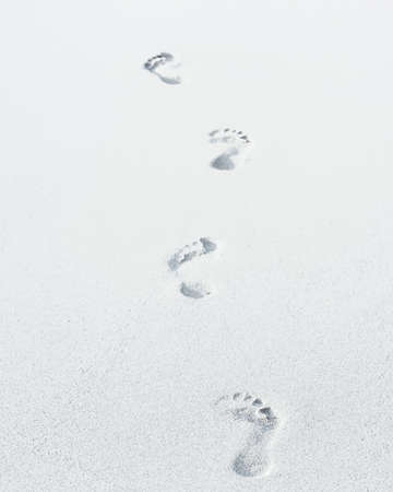Barefooted footprints on the white sand of the beach, at the coastline.