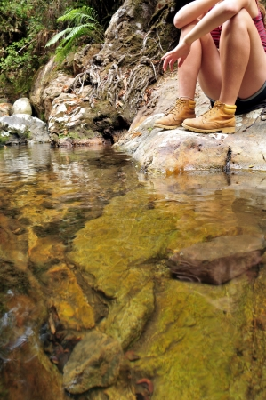 A young girl sitting at a stream in the mountains