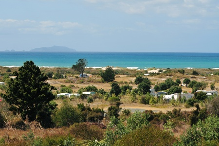 Large area campsite with tents, caravans and motorhomes scattered among threes and bushes with ocean and island in background