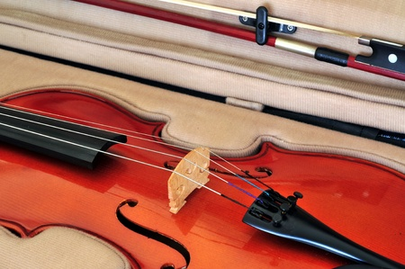 Viola in its case showing f-holes, bridge, fingerboard, chinrest, tailpiece with fine tuners and bow Stock Photo