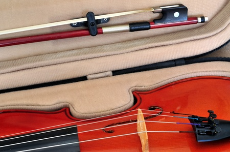 Viola in its case showing f-holes, bridge, fingerboard, tailpiece with fine tuners and bow