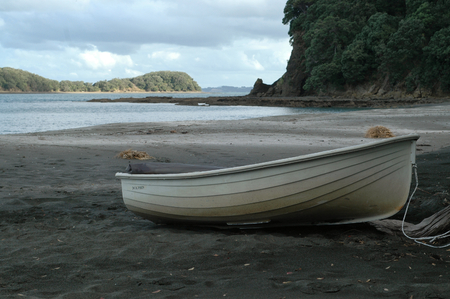 Small rowing boat on sandy beach at low tide