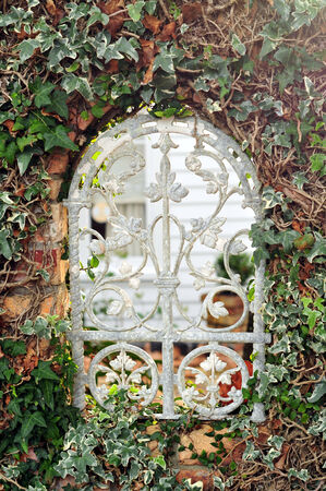 Ornamented ancient window in garden fence Stock Photo
