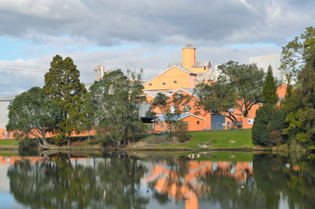 Factory in pleasasant environment of park with pond