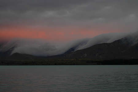 Thick evening fog coming down valleys of Southern Alps
