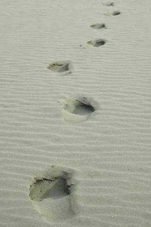 Human footsteps in light grey sand
