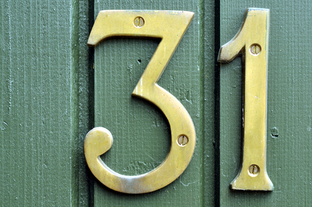 screwed: Old brass numbers screwed onto a green wooden house wall Stock Photo